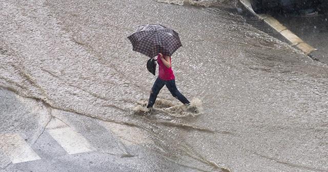 Woman walking through flooded street in the rain