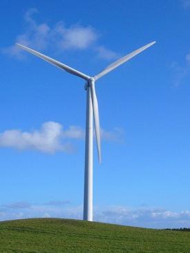 wind turbine grassy hill blue sky