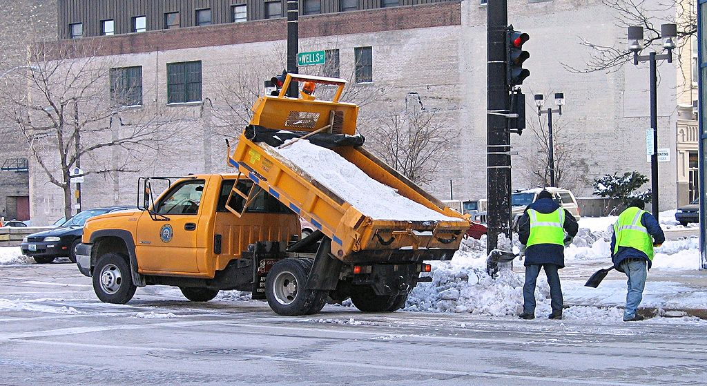 yellow salt truck dumping salt in street