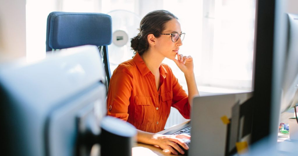 woman in orange shirt at computer