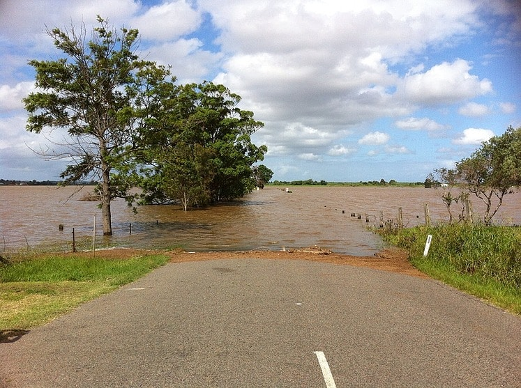 flooded rural road with fence lines