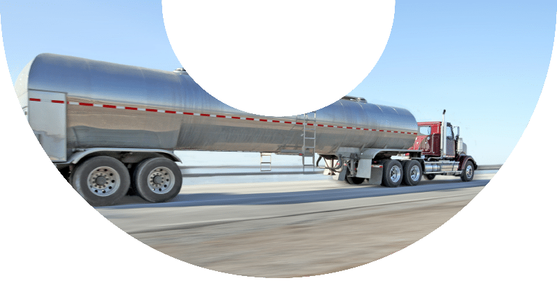 red fuel truck with red and white stripe on tank in motion
