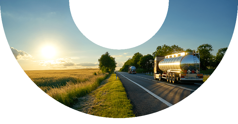 two fuel trucks driving down rural interstate road at sunset