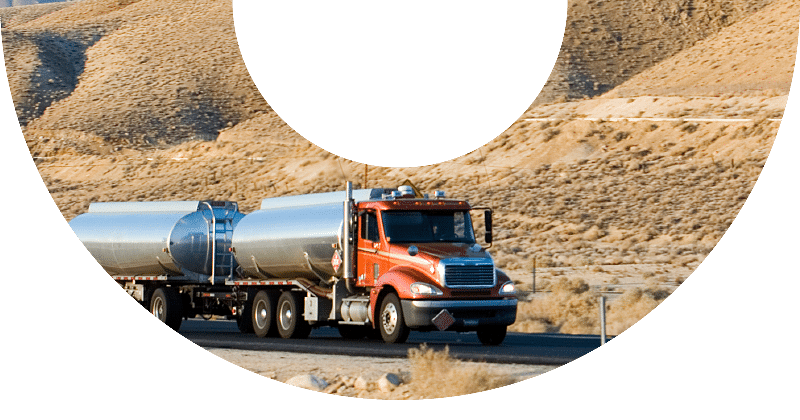 amber truck with two tanks driving down desert road
