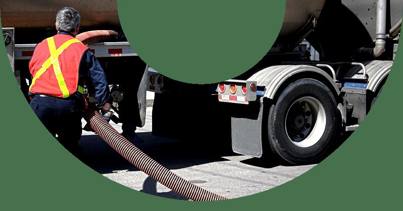 man in orange vest attaching hose to fuel truck