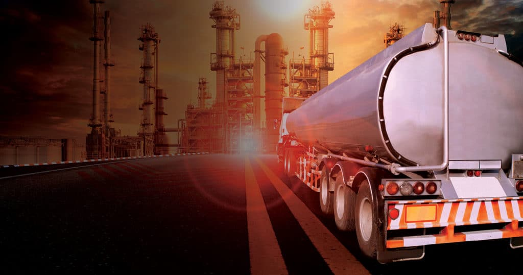 gas truck driving towards refinery at sunset