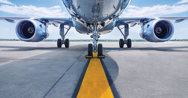 airplane chrome underside on runway with yellow pavement stripe
