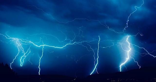 vivid night blue sky lightning over city lights