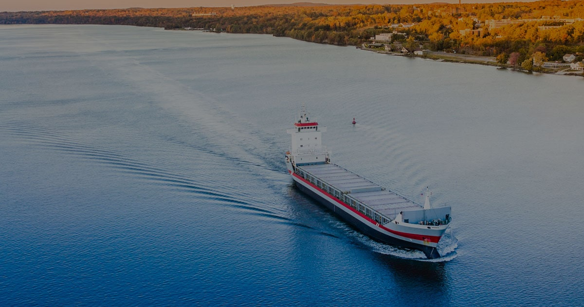 RouteGuard cargo ship with red stripe near land