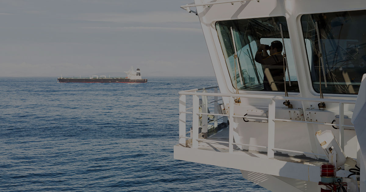 RouteGuard ship captain looking out window at ocean with binoculars