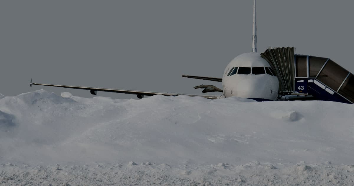 RunwayMaster airplane covered up to wings in snow