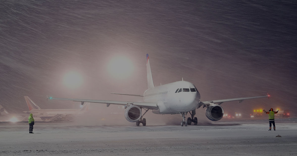 RunwayMaster commercial airplane being directed on runway heavy blowing snow