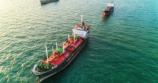 aerial of red gas tanker on green ocean