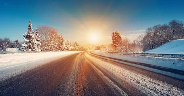 Sun rising over a plowed road