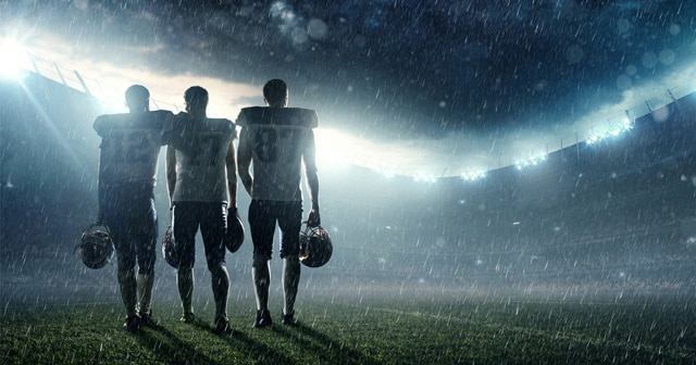 Football players on rainy field