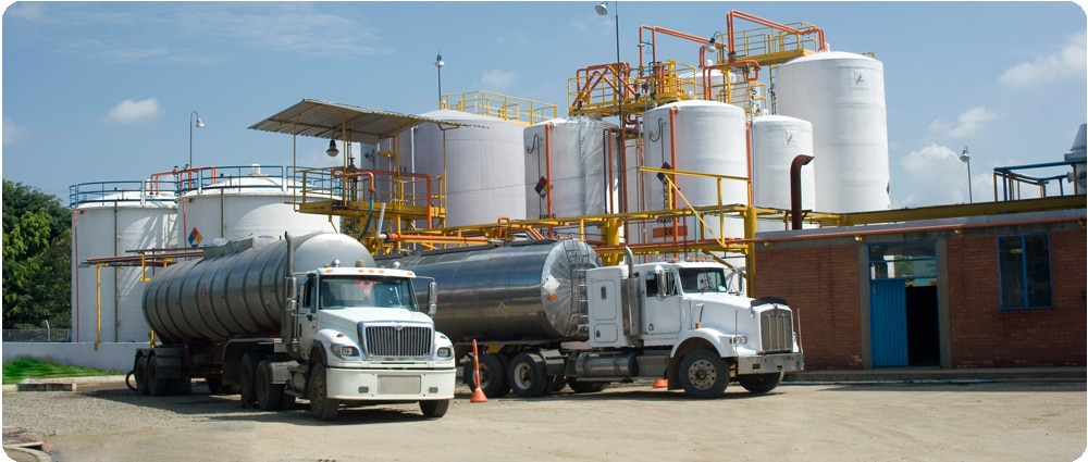 Two fuel trucks in front of storage tanks