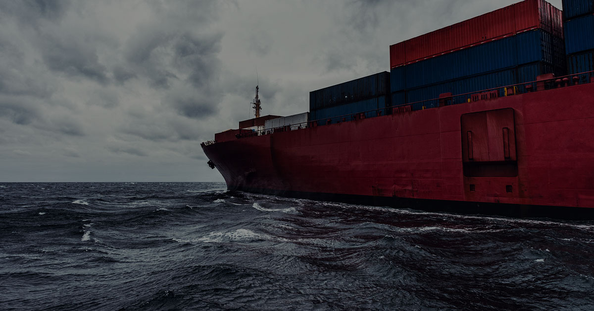 A container ship navigates the North Atlantic under dramatic skies. Wide angle view taken at sea level.