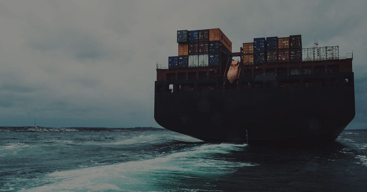A 200m (600') long container ship navigates the North Atlantic under dramatic skies. Wide angle view taken at sea level.