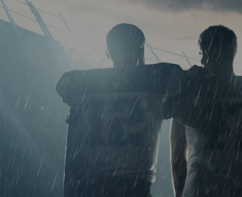 football players in rain at stadium
