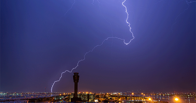 Air traffic control tower with lightning in the sky