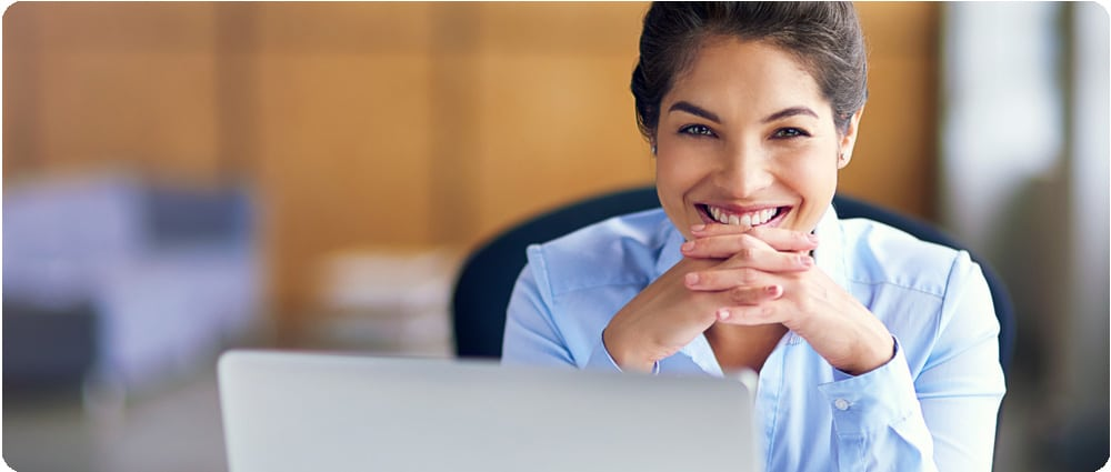 Business woman smiling behind laptop