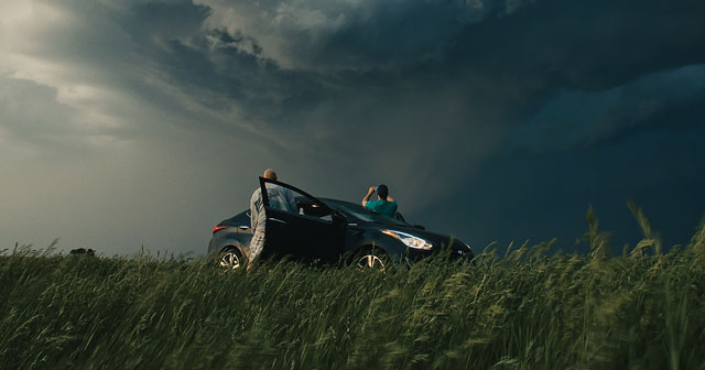 News Insights MN Monthly car parked with storm clouds