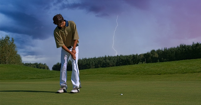 Golfer putting with lightning in background