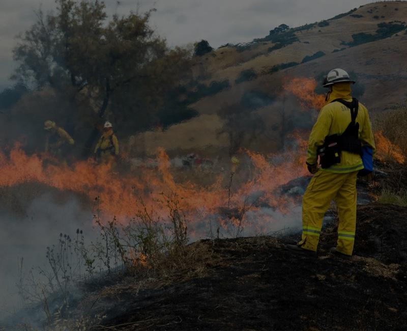 Firefighter facing fire outdoors