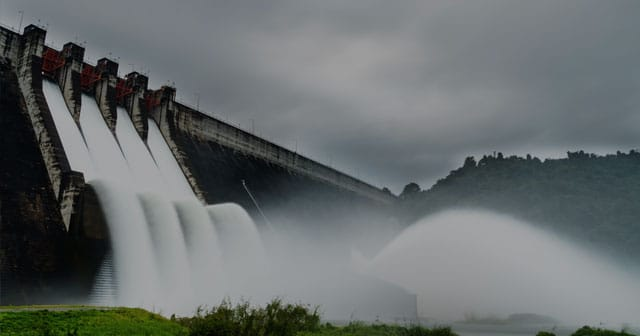 dam water spillway red gates dark sky