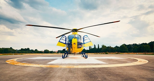 yellow helicopter on pad cloudy sky background