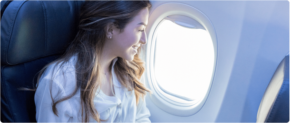 woman smiling out of airplane window