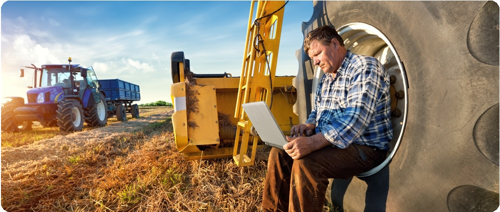 Farmer on laptop next to tractor