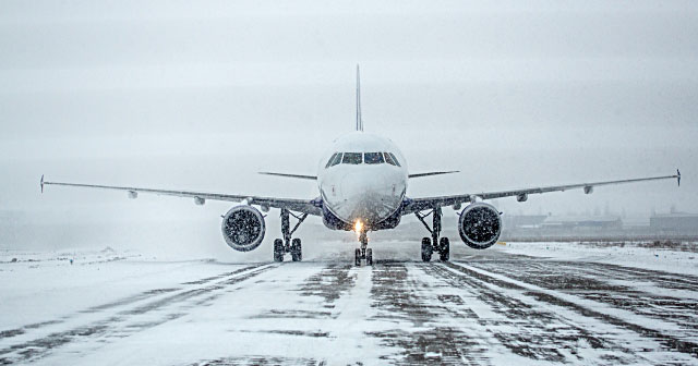 commercial airplane on snowy and icy runway
