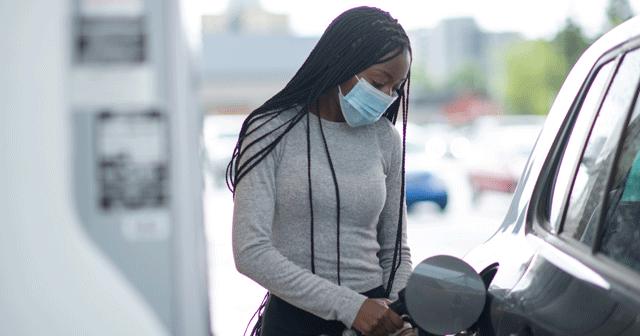 Blog Header Woman wearing mask while pumping gas