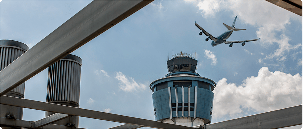 Airplane flying over control tower