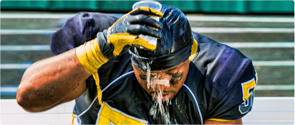 Overheated football player pouring water on his head
