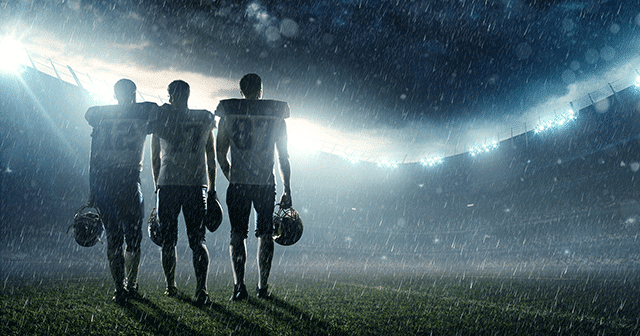 Football players standing on the field in the rain