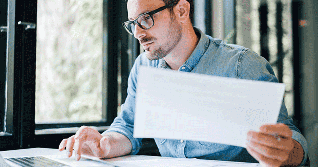 News Insights Man on computer holding paperwork
