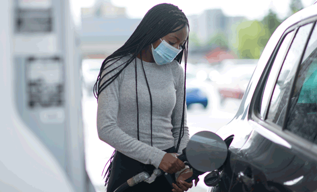 Young woman wearing mask while pumping gas