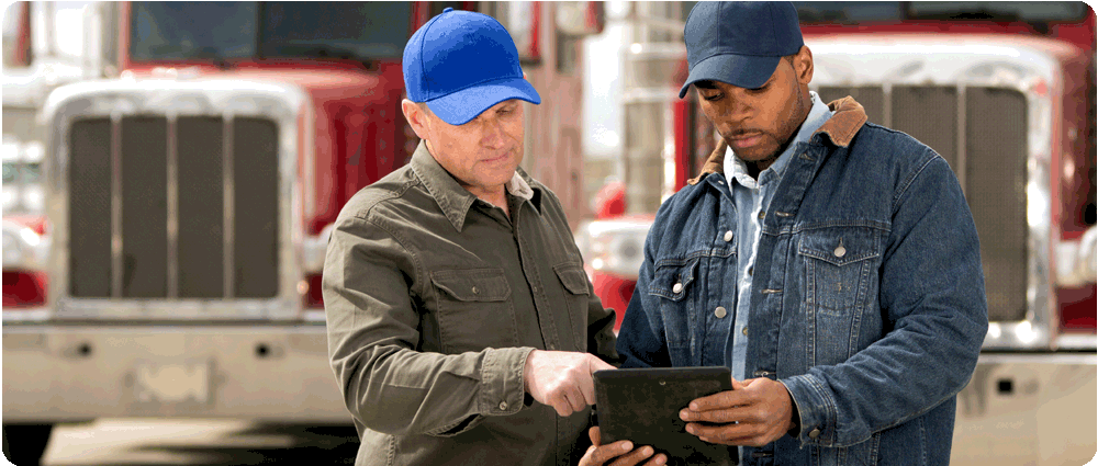 Fuel truck drivers looking at tablet