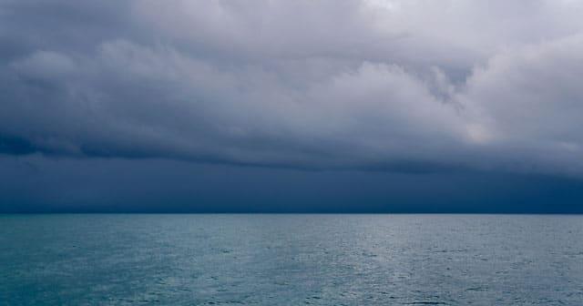 dark blue threatening skies over calm ocean